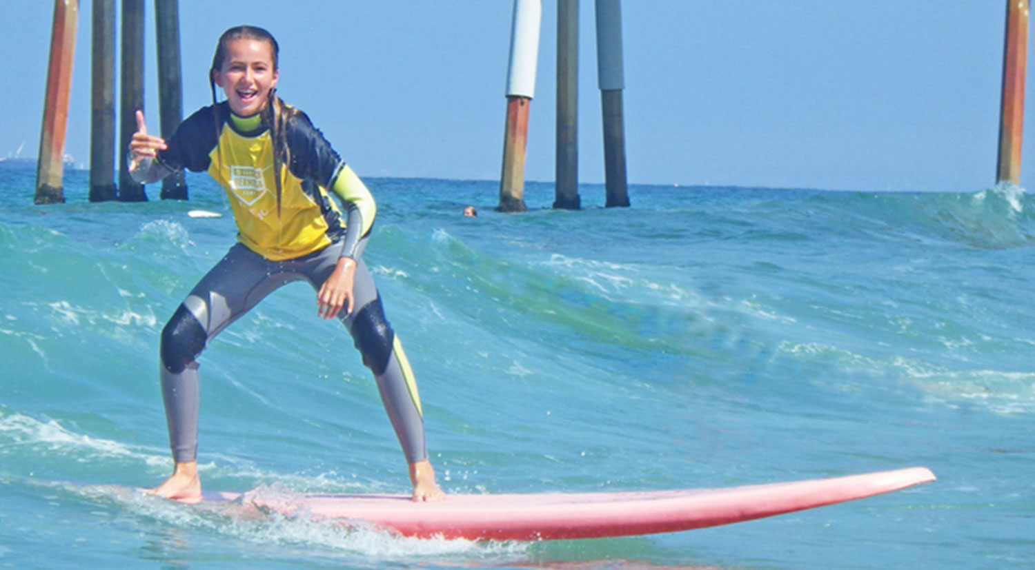 young girl smiling while surfing